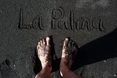 Feet standing on a black sand beach of La Palma. Canary islands, Spain Royalty Free Stock Image
