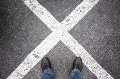 Feet standing on dark urban asphalt with crossing lines stock photo