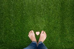 Feet standing on grass with small heart Royalty Free Stock Photos