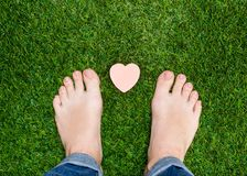Feet standing on grass with small heart Stock Image