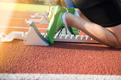 Feet on starting block ready for a spring start. Focus on leg of a athlete about to start a race in stadium with sun flare Royalty Free Stock Photos