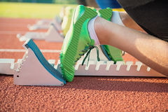 Feet on starting block ready for a spring start. Focus on leg of a athlete about to start a race in stadium with sun flare Royalty Free Stock Images