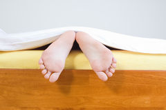 Feet sticking out from blanket. A closeup view of two bare feet sticking out from under a blanket at the end of a bed Stock Image