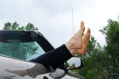 Feet sticking out a car window Stock Image