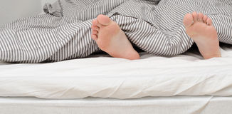 Feet sticking out from covered Royalty Free Stock Photo
