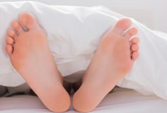 Feet sticking out from the duvet Stock Photo