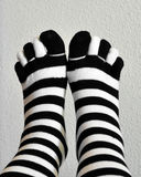 Feet in stockings black and white striped Royalty Free Stock Image