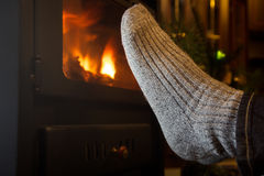 Feet in stockings by the fireplace Royalty Free Stock Photography