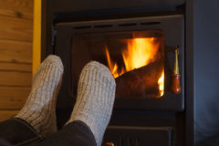 Feet in stockings by the fireplace Stock Photo