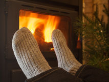 Feet in stockings by the fireplace Royalty Free Stock Image