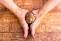 Feet with Stone. Two feet together holding a stone in the middle on a wooden background Royalty Free Stock Image