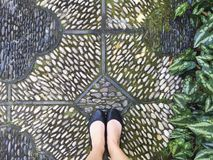 Feet on a stone path. Woman wearing black flats on a stone royalty free stock images
