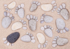 Feet by stones. Many stone feet on sand Stock Images
