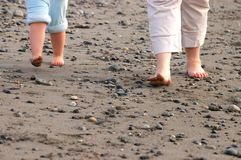 Feet on stony beach. Feet of two barefoot people walking on stony beach Stock Image