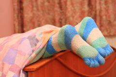 Feet with striped socks. Finger in bed Stock Photography