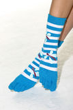 Feet with striped toe socks. Striped wool toe socks in blue and white shot in the studio Royalty Free Stock Image