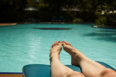 Feet of a sunbathing woman at sunbed next to a swimming pool Stock Photography