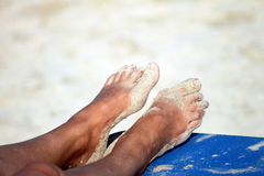 Feet of sunburnt woman on beach Stock Image