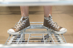 Feet on supermarket trolley Stock Photos