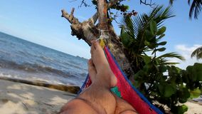 Feet swinging in a hammock on a caribbean tropical beach, POV. Livingston, Guatemala. Feet swinging in a hammock on a caribbean tropical beach, POV. Playa stock footage