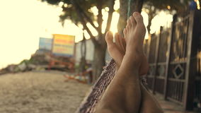 Feet swinging in a hammock, POV. Relaxing on the beach at sunset. stock video footage