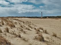 Cape Hatteras Lighthouse behind the Dunes. At 198 feet tall, Cape Hatteras Lighthouse is the tallest brick lighthouse in North America and a climb of 268 steps Stock Image
