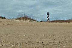 Cape Hatteras Lighthouse behind the Dunes. At 198 feet tall, Cape Hatteras Lighthouse is the tallest brick lighthouse in North America and a climb of 268 steps Stock Photo