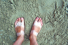 Feet with tanlines from sandals in sand. A holiday concept, a pair of feet with tanlines from sandals buried in sand with toys on the beach Stock Photography