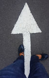Feet on tarmac road. With white direction arrow stock photos