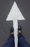 Feet on tarmac road. With white direction arrow royalty free stock image