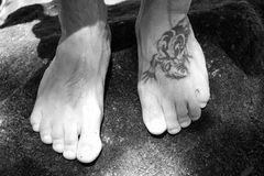 Feet and tattoo. Black and white feet and a big tattoo royalty free stock photo