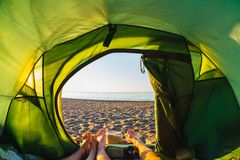 Feet out of a tent overlooking the seashore royalty free stock image