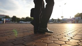 Feet of three businessmen walking in city with sun flare at background. Business men commute to work together. Confident. Guys being on his way to office stock video