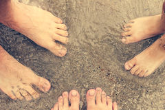 Feet of three people standing in the sea. Family resting on the beach and swimming in the sea Stock Photos
