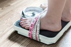 Feet tied up with measuring tape to a weight scale. Addiction and obsession to weight loss. Anorexia and eating disorder concept Stock Images