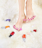 Feet in toe separators. Body part shot of healthy woman's feet in pedicure toe separators with vials of nail olish around Stock Image