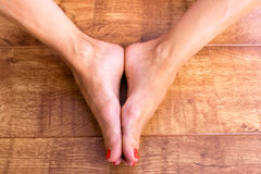Feet Together. Two feet placed together on a wodden background Royalty Free Stock Images