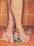 Feet of together washing bodies in shower room. Female and male feet of together washing bodies in shower room. Feet on red tilles selective focus on toes stock images