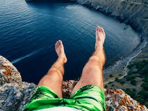 Feet tourist sitting on top of the mountain against the sea royalty free stock images