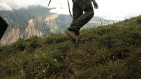 Feet tourists walking on a mountain trail. Hiking in the mountains. HD stock video footage