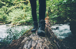 Feet trekking boots Traveler alone crossing over river stock photo
