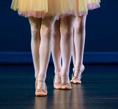 Feet of trio  of dancers in flat shoes. And yellow and pink skirts Royalty Free Stock Photos