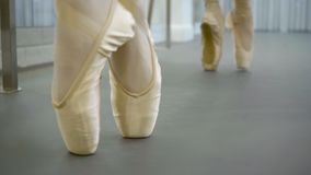 The feet of two ballerinas in silk pointe doing pour be bourree in the ballet studio. The dancers stand near the barre and the mirror and exersices beautiful stock video