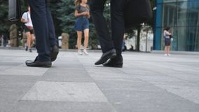 Feet of two businessmen walking in city street. Business men commute to work together. Confident guys being on his way. To office. Legs of colleagues going stock video footage