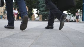 Feet of two businessmen walking in city street. Business men commute to work together. Confident guys being on his way. To office. Legs of colleagues going Stock Images