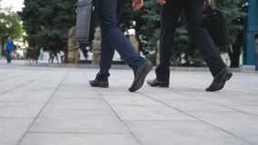 Feet of two businessmen walking in city street. Business men commute to work together. Confident guys being on his way. To office. Legs of colleagues going Royalty Free Stock Photo