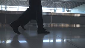 Feet of two businessmen walking at terminal of airport. Legs of business men stepping together. Colleagues going indoors. Slow motion Low angle of view Close stock footage