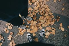 Feet of two people wearing sneakers standing on fallen leaves on cement royalty free stock images
