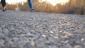 Feet of two women running at country road. Two young girls jogging outdoors. Female athletes training together at nature. Healthy active lifestyle. Low angle stock video footage