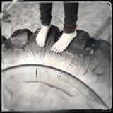 Feet on tyre Stock Photo